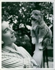 A woman holding a puppy.