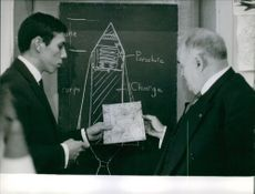 A man showing a picture to another man on paper. 1960