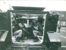 Man sitting inside a service van being guarded by military men in Riotsville, USA.