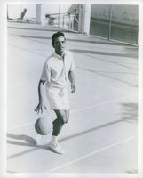 American Jazz singer Johnny Mathis seen dribbling the ball at the basketball court