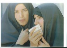 Two shiite woman talk as they wait to vote.